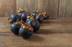 Purpurrote Mangostanfrüchte auf hölzernem Hintergrund Stockbild