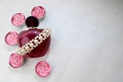 Purpurrote schöne transparente Glasflasche weibliches Parfüm verziert mit weißen graubraunen Perlen und rosa Paraffinkerzen in de stockfotos