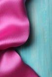 Purpurrote Seide auf hölzernem Hintergrund Stockbild