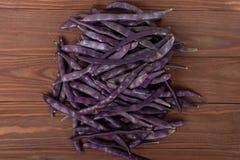 Purpurrote Stangenbohnen auf einem hölzernen Hintergrund Stockbild