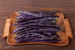 purpurrote Stangenbohnen auf einer hölzernen Platte auf einem hölzernen Hintergrund Stockbilder