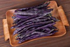 purpurrote Stangenbohnen auf einer hölzernen Platte auf einem hölzernen Hintergrund Lizenzfreie Stockfotos