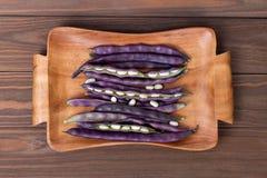 purpurrote Stangenbohnen auf einer hölzernen Platte auf einem hölzernen Hintergrund Lizenzfreie Stockbilder