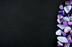 Purpurrote Steine auf schwarzem Hintergrund Stockbilder