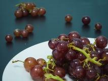 Purpurrote Trauben auf weißer Platte auf der schwarzen Tabelle Lizenzfreie Stockbilder
