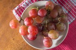 Purpurrote Traubengruppe auf Teller. Stockbild