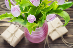 Purpurrote Tulpen mit Geschenken auf dem Holztisch Stockfoto
