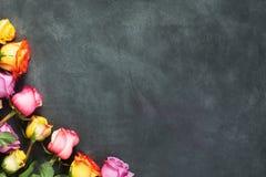 Purpurrote und gelbe Rosen, packen Geschenk auf schwarzem Hintergrund ein Stockfotografie