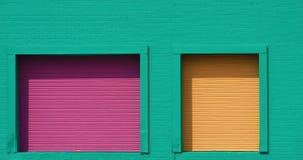 Purpurrote und gelbe Türen auf grüner Wand Stockbild