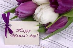 Purpurrote und weiße Tulpen mit Weißbuch auf einem weißen hölzernen Hintergrund und einer Karte glückliches Frauen ` s Tagesengli Stockfotos