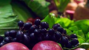 Purpurrote Videotrauben mit den Früchten und grünem Gemüse, die auf Tabelle einstellen stock footage