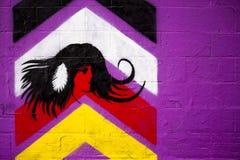 Purpurrote Wand mit Grafik des amerikanischen Ureinwohners auf Graffitiwand Stockbilder