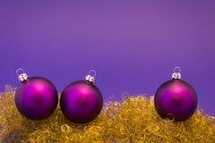 Purpurrote Weihnachtsbälle auf Goldfunkeln Lizenzfreie Stockfotografie