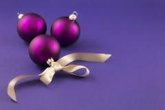 Purpurrote Weihnachtsbälle mit grauem Band Stockbilder
