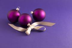Purpurrote Weihnachtsbälle mit grauem Band Stockfoto