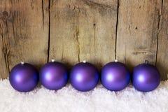 Purpurrote Weihnachtsbälle mit Schnee Stockfotografie