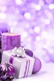 Purpurrote Weihnachtsszene mit Flitter, Geschenk und Kerzen Stockbild