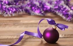 Purpurroter Ball des Weihnachtsspielzeugs mit Band und Lametta Lizenzfreies Stockbild
