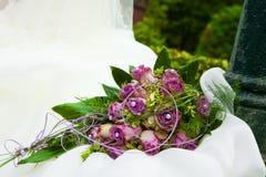 Purpurroter Blumenstrauß auf weißem Kleid Stockfoto