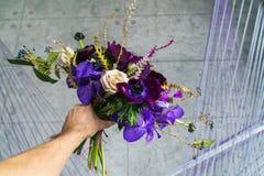 Purpurroter Hochzeitsblumenstrauß in der Mann ` s Hand Heiratstendenzen Lizenzfreies Stockbild