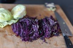 Purpurroter Kohl fein gehackt mit einem Kohlsauerkraut auf einem hölzernen hackenden Brett, Messer im Hintergrund gekocht werden stockbild