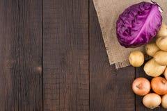 Purpurroter Kohl, Kartoffeln und Zwiebeln auf einer alten dunklen hölzernen Tabelle Stockfotos