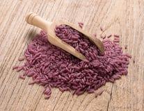 Purpurroter Reis auf hölzernem Hintergrund Stockfotografie