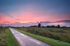 Purpurroter Sonnenaufgang über niederländischem Ackerland mit Windmühle Lizenzfreie Stockfotografie