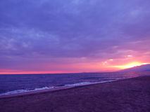 Purpurroter Sonnenuntergang auf italienischem Strand lizenzfreies stockbild