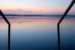 Purpurroter Sonnenuntergang am Balaton See im assimetric Geländer des Sommers führt im Wasser Lizenzfreie Stockfotografie