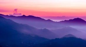 Purpurroter Sonnenuntergang in den Bergen Stockbilder