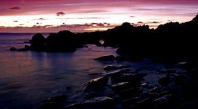 Purpurroter Sonnenuntergang mit eindeutigen Felsen Stockbild