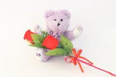 Purpurroter Teddybär und rote Rosen Lizenzfreies Stockfoto