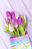 Purpurroter Tulpenblumenstrauß in der Geschenktasche Lizenzfreie Stockbilder