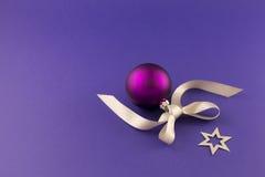 Purpurroter Weihnachtsball mit Stern und grauem Band Lizenzfreie Stockbilder