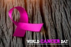Purpurrotes Band auf hölzernem Hintergrund für Weltkrebstag Lizenzfreie Stockfotos