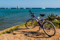 Purpurrotes Fahrrad nahe der Küstenlinie mit Meer und den Booten im Hintergrund lizenzfreies stockbild