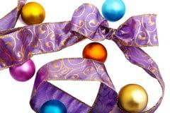 Purpurrotes Farbband mit colourfull Weihnachtskugeln Stockfotografie