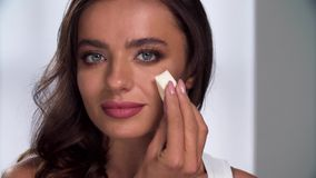 Purpurrotes Make-up und bunte helle Nägel Frau, die Ton auf Gesicht mit Schwammnahaufnahme anwendet stock video