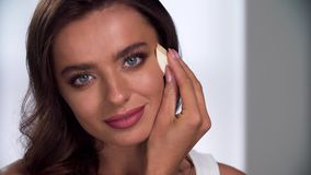 Purpurrotes Make-up und bunte helle Nägel Frau, die Ton auf Gesicht mit Schwammnahaufnahme anwendet stock video footage