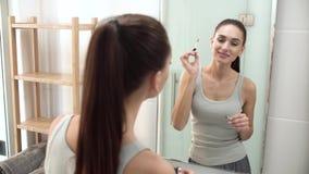 Purpurrotes Make-up und bunte helle Nägel Frauen-bürstende Augenbrauen am Badezimmer-Spiegel stock video