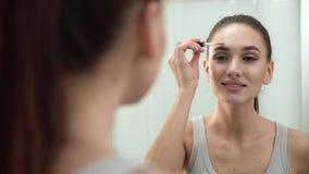 Purpurrotes Make-up und bunte helle Nägel Frauen-bürstende Augenbrauen am Badezimmer-Spiegel stock video footage