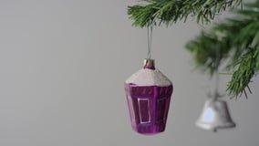 Purpurrotes Weihnachtsspielzeug und silberne Glocke auf dem Weihnachtsbaumast stock video footage