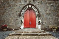 Purpury kwitną dekorację umieszczającą przy czerwonym drzwi Zdjęcie Stock