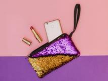 Purpury z złocistą kobiety ` s torebką z telefonem i otwartą pomadką na dwa koloru stole Pastelowy kolor Mieszkanie nieatutowy obraz royalty free