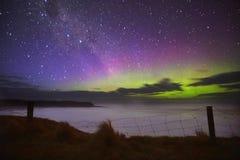 Purpury zielona zorza nad falezy ogrodzeniem fotografia stock