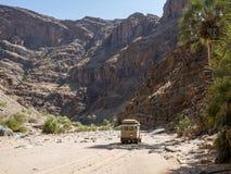 Purros, Namíbia - 26 de julho de 2015: condução de veículo 4x4 offroad na cama de rio seca do rio de Hoarusib com montanhas Imagens de Stock