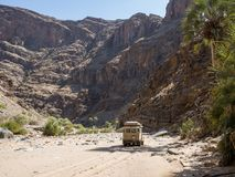 Purros, Namibia - July 26, 2015: 4x4 offroad vehicle driving in dry river bed of Hoarusib River with mountains. In background stock images