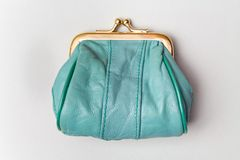Purse for coins.Wallet for change. Leather purse. Turquoise purse on a grey background. Color of the trend.The concept of poverty.  royalty free stock photos