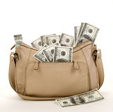 Purse Full of Money. A tan purse stuffed full of money on a white background royalty free stock photography
